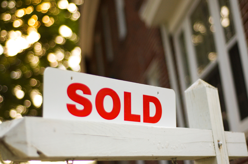 "Real Estate ""sold"" sign with red brick building and trees blurry in the background"