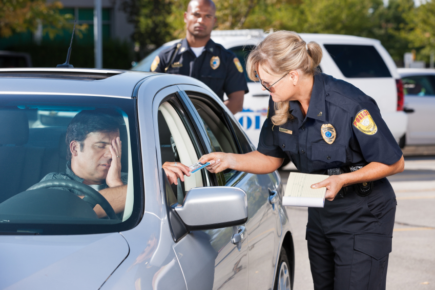 A mature female law enforcement officer stands by a vehcile she has stopped and takes the driver's license from a middle aged man while her partner stands by in the background.